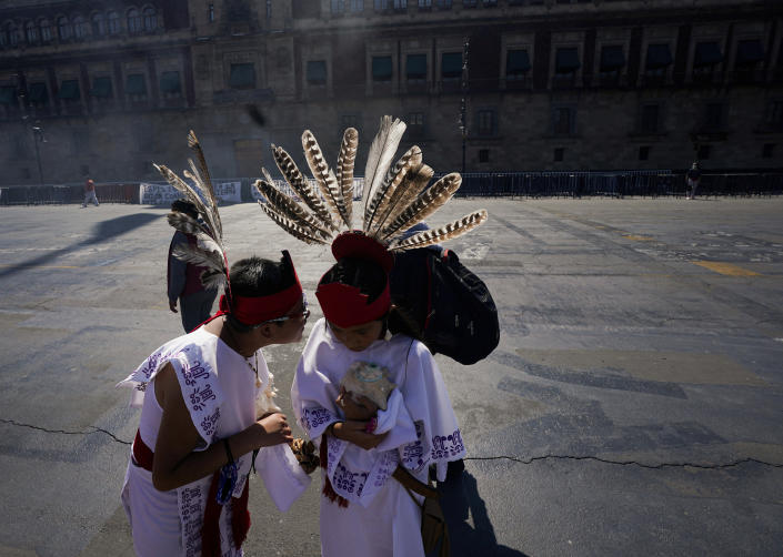 Two young dancers speak prior a performance as part of the commemoration marking the 700 year anniversary of the founding of the Aztec city of Tenochtitlan, known today as Mexico City, at Zocalo square in Mexico City, Monday, July 26, 2021, amid the new coronavirus pandemic. (AP Photo/Fernando Llano)