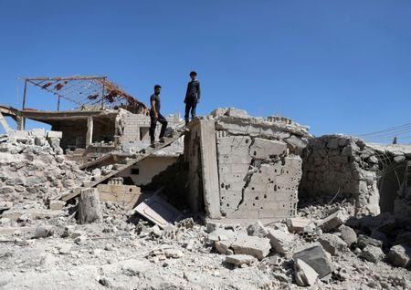 FILE PHOTO: Men inspect a damaged house in Busra al-Harir town, near Deraa