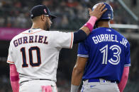 Houston Astros first baseman Yuli Gurriel (10) taps the helmet of his brother, Toronto Blue Jays' Lourdes Gurriel Jr., during the fifth inning of a baseball game, Sunday, May 9, 2021, in Houston. (AP Photo/Eric Christian Smith)