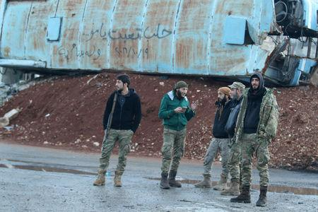 "Rebel fighters stand near a damaged bus used as a barricade in the rebel-held besieged Bab al-Hadid neighbourhood of Aleppo, Syria December 2, 2016. The graffiti on the bus reads in Arabic: ""Aleppo is tired mother...19/10/2016 and we still want freedom."" REUTERS/Abdalrhman Ismail"
