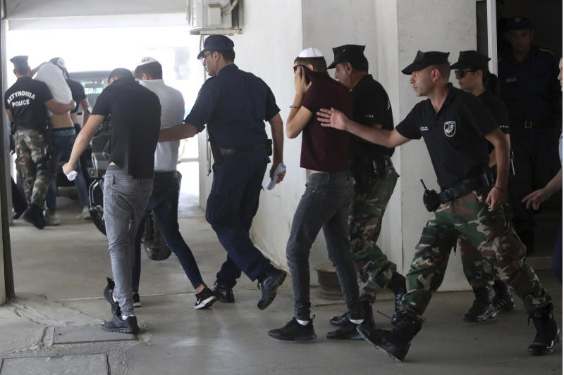 Suspects cover their faces with their shirts as they arrive at the Famagusta courthouse in Paralamni, Cyprus, Friday, July 26, 2019. A Cyprus court has extended the detention of seven Israeli teenagers out of the 12 who were arrested as suspects in the rape of a 19-year-old British woman. (AP Photo/Petros Karadjias)
