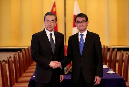Chinese State Councilor and Foreign Minister Wang shakes hands with Japan's Foreign Minister Kono at their meeting in Tokyo