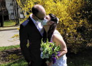 In this April 11, 2020, photo provided by Michael Wargo, newlyweds Danielle Cartaxo and Ryan Cignarella kiss while wearing masks after getting married in West Orange, N.J. Barred from getting married in a public space due to lockdown restrictions, Cartaxo and Cignarella got married on the front lawn of the home of a stranger who offered to help. (Michael Wargo via AP)