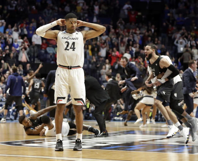 Cincinnati forward Kyle Washington stands on the court as Nevada celebrates its comeback victory in the Round of 32. (AP)