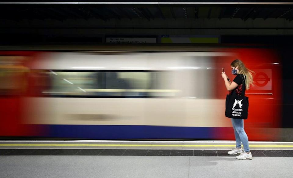 A passenger photographs the arrival of a Northern Line tube train at the newly opened Nine Elms underground station (REUTERS)