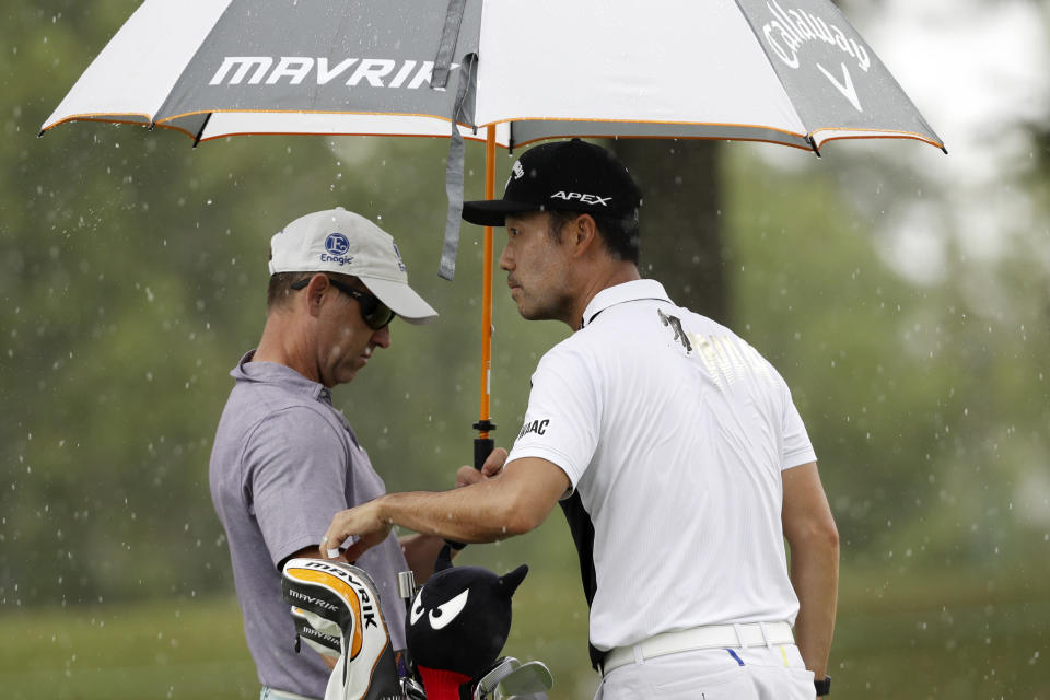 Kevin Na and his caddie try to wait out a rain shower on practice day at the World Golf Championship-FedEx St. Jude Invitational Wednesday, July 29, 2020, in Memphis, Tenn. (AP Photo/Mark Humphrey)