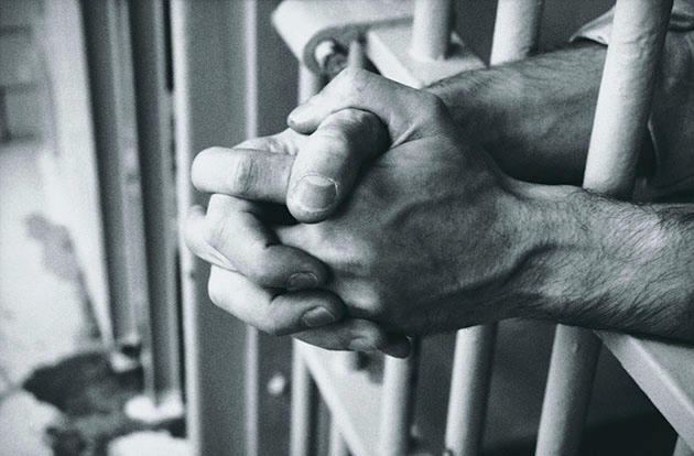 File photo of hands resting on prison bars (Dick Luria/Thinkstock)