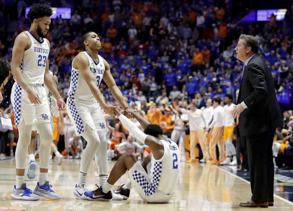 Kentucky guard Ashton Hagans (2) is helped up by Keldon Johnson (3) after Hagans was called for a foul in the final minute of an NCAA college basketball game against Tennessee at the Southeastern Conference tournament Saturday, March 16, 2019, in Nashville, Tenn. Kentucky head coach John Calipari is at right and EJ Montgomery (23) is at left. Tennessee won 82-78. (AP Photo/Mark Humphrey)