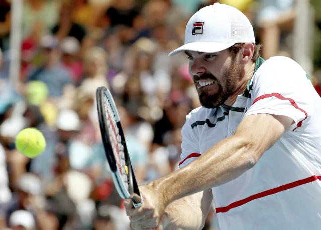 Reilly Opelka of the U.S. makes a backhand return to Italy's Fabio Fognini during their first round singles match at the Australian Open tennis championship in Melbourne, Australia, Tuesday, Jan. 21, 2020. (AP Photo/Dita Alangkara)