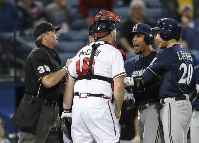 Milwaukee Brewers' Carlos Gomez (27) and Atlanta Braves catcher Brian McCann (16) are separated by home plate umpire Paul Nauert and Brewers' Jonathan Lucroy (20) as they exchange words following a home run by Gomez in the first inning of a baseball game Wednesday, Sept. 25, 2013 in Atlanta. (AP Photo/John Bazemore)