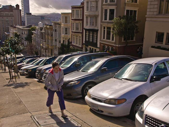 A woman walks up a hill alongside parked cars in San Francisco.