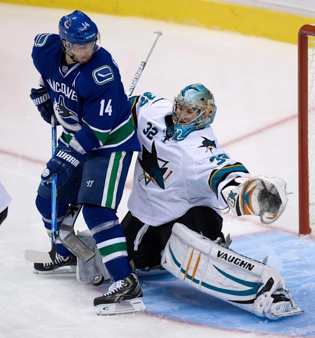 San Jose Sharks' goalie Alex Stalock, right, of Finland, makes the save while being screened by Vancouver Canucks' Alex Burrows during second period pre-season NHL hockey action in Vancouver, British Columbia on Monday Sept. 16, 2013. (AP Photo/The Canadian Press, Darryl Dyck)