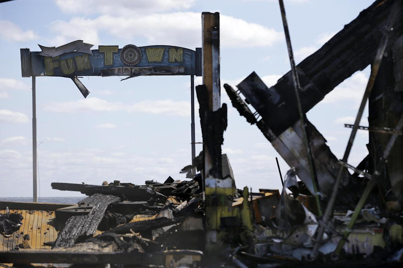 FILE - In this Tuesday, Sept. 17, 2013, file photograph, the sign for Funtown Pier stands above charred rubble in Seaside Park, N.J., after a fire that started near a frozen custard stand on the boardwalk. The historic Jersey shore pier that was pummelled by Superstorm Sandy, then destroyed in a spectacular fire may finally be done in by building regulations. The owner of the former Funtown Pier said he won't rebuild it if the town sticks to height restrictions it wants to impose on rides on a rebuilt pier. (AP Photo/Mel Evans, File)
