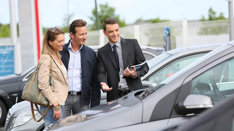 Car dealership salesman showing vehicles to couple