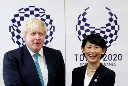 Britain's Foreign Secretary Boris Johnson smiles with Japan's Minister in charge of overseeing preparations for Tokyo's 2020 Summer Olympic Games Tamayo Marukawa in front of Tokyo 2020 Olympics and Paralympics emblems during their meeting in Tokyo, Japan July 21, 2017. REUTERS/Issei Kato