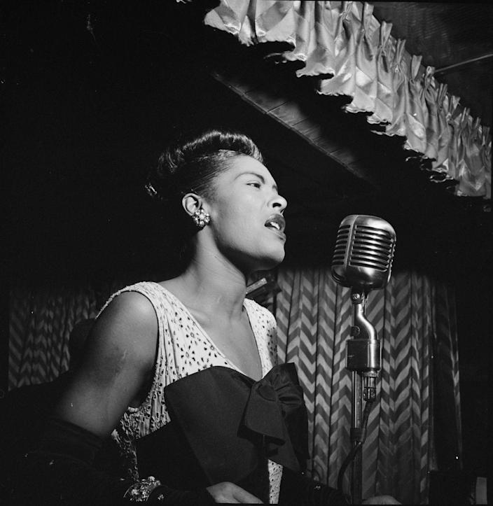 <p>Jazz singer Billie Holiday performs at the Club Downbeat in New York wearing a V-neck dress with a large bow.</p>