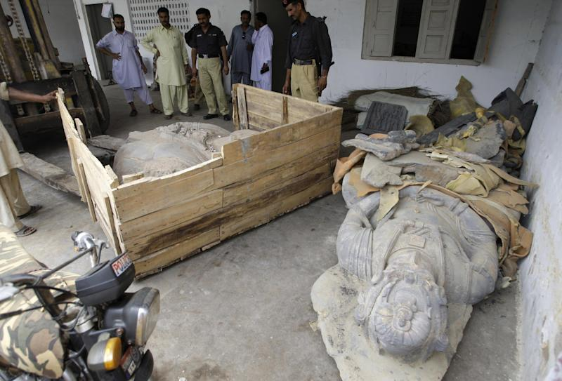 In this photo taken on July 6, 2012, Pakistani officials look at Buddha statues confiscated by custom authorities in Karachi, Pakistan. Lacking the necessary cash and manpower, Pakistan is struggling to stem the flow of millions of dollars in ancient Buddhist artifacts that shadowy criminal gangs dig up from the country's northwest and smuggle to collectors around the world. (AP Photo/B.K. Shakil Adil)