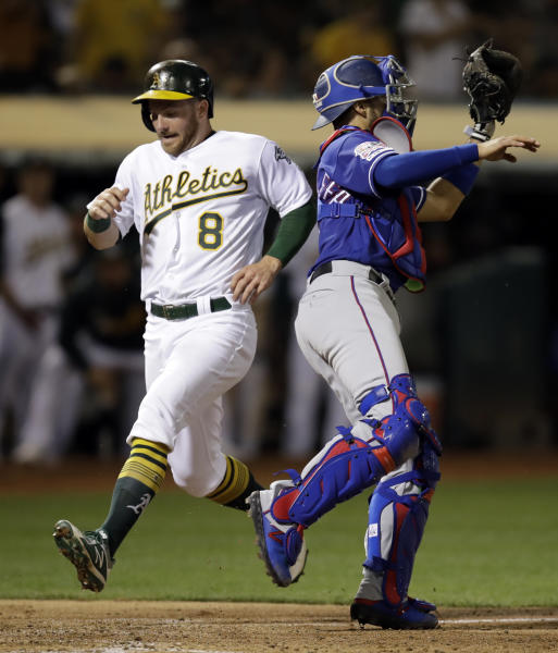 Oakland Athletics' Robbie Grossman (8) scores behind Texas Rangers catcher Isiah Kiner-Falefa, right, in the fourth inning of a baseball game, Tuesday, April 23, 2019, in Oakland, Calif. Grossman scored on a two-run double by Oakland's Marcus Semien. (AP Photo/Ben Margot)