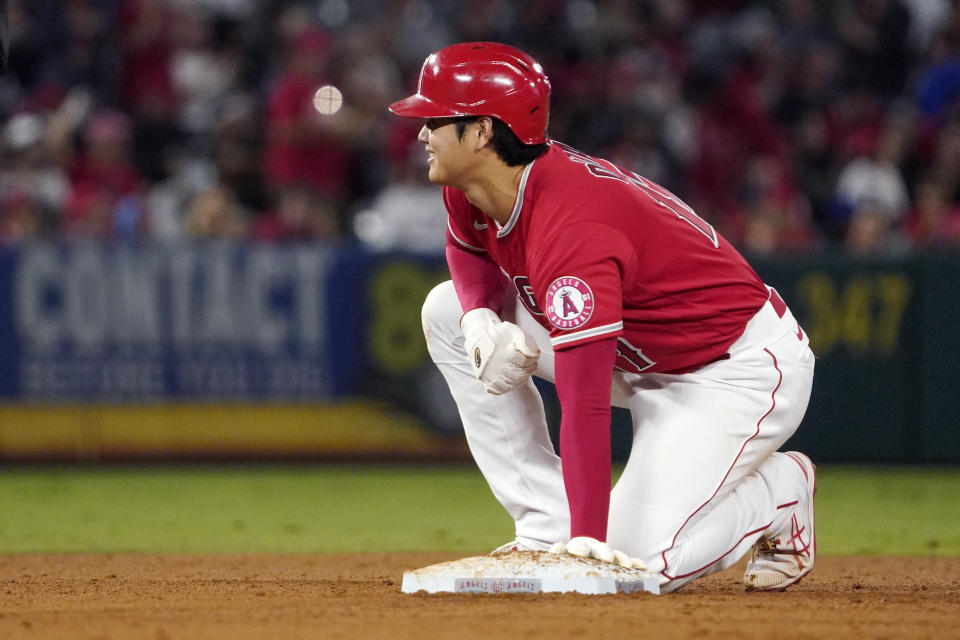 Los Angeles Angels designated hitter Shohei Ohtani kneels on second base after advancing from first on a single by Phil Gosselin during the third inning of a baseball game against the Seattle Mariners Saturday, Sept. 25, 2021, in Anaheim, Calif. (AP Photo/Mark J. Terrill)