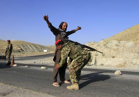 An Afghan National Army soldier (ANA) inspects passengers at a checkpoint on the outskirts of Jalalabad province June 29, 2015. REUTERS/Parwiz