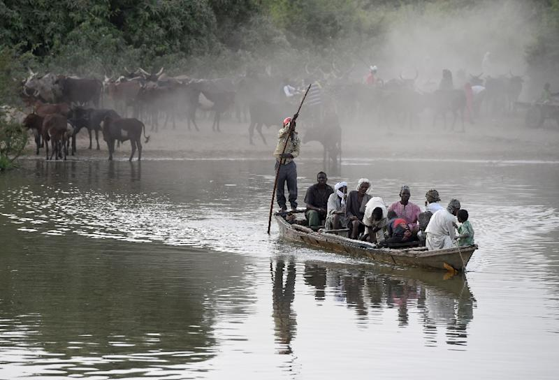 A picture taken on March 30, 2015 shows people riding a boat to cross a section of Lake Chad whose waters border Niger, Nigeria and Cameroon in the village of Guite