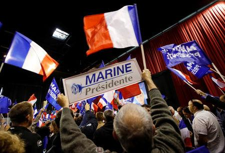 Supporters of Marine Le Pen, French National Front (FN) political party leader and candidate for French 2017 presidential election, hold French flags and posters during a political rally in Perpignan, France, April 15, 2017.  REUTERS/Jean-Paul Pelissier