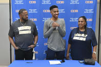In this Jan. 31, 2020, photo provided by Tim Foster, Savion Johnson, center, stands with his father Patrick, left, and mother, Sabrina, after he signed his acceptance letter to Notre Dame de Namur University during a ceremony at the College of the Sequoias gym in Visalia, Calif. Savion was set to transfer this fall from a junior college in California to Notre Dame de Namur University in the San Francisco Bay Area as a Division 2 basketball recruit. As the coronavirus spread, Johnson received a text from the basketball coach rescinding his offer. The school, immersed in deep financial problems amid dwindling enrollment, decided to cancel the incoming freshman class and competitive sports as it tries to avert total closure. (Tim Foster via AP)