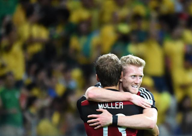 Germany's forward Andre Schuerrle (R) is congratulated by forward Thomas Mueller after scoring during the semi-final football match between Brazil and Germany at The Mineirao Stadium in Belo Horizonte on July 8, 2014 (AFP Photo/Christophe Simon)