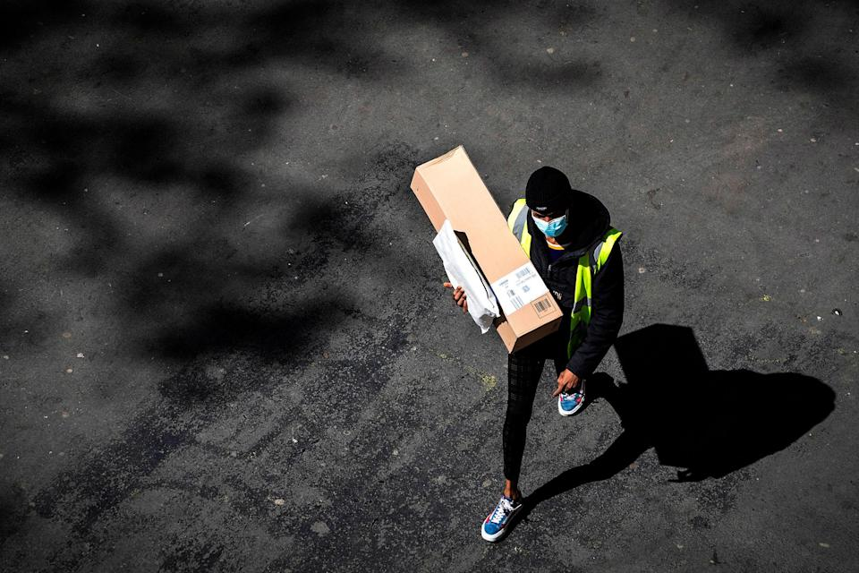 A delivery man wearing a protective mask carries an Amazon box and a letter in a street of Paris on April 15, 2020 on the 30th day of a lockdown in France aimed at curbing the spread of the COVID-19 infection caused by the novel coronavirus. (Photo by JOEL SAGET / AFP)