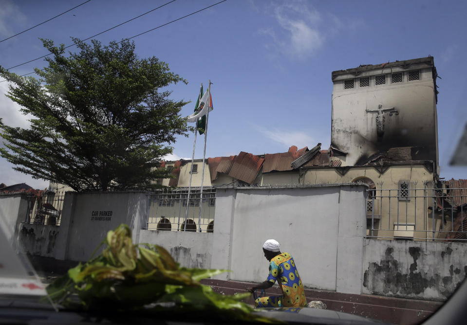A man rides a bicycle past a burnt Court of Appeal building in Lagos, Nigeria, Thursday Oct. 22, 2020. Lagos streets were empty and shops were shuttered Thursday, as residents of Nigeria's largest city obeyed the government's curfew, stopping the protests against police brutality that had lasted for two weeks. ( AP Photo/Sunday Alamba)