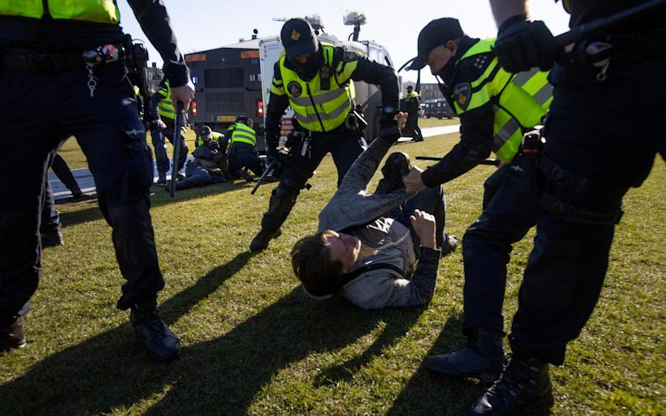 Dutch police arrested several demonstrators as they broke up a demonstration of several hundred of people who protested against the coronavirus lockdown and curfew on Museum Square in Amsterdam, Netherlands, - AP Photo/Peter Dejong
