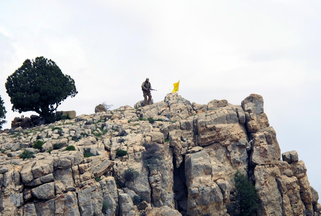 """<p> FILE - In this May 9, 2015 file photo, a Hezbollah fighter stands on a hill next to the group's yellow flag in the mountainous region of Qalamoun, in Assal al-Ward Syria. The Middle East may have turned a page with the defeat of the Islamic State group in its former """"capital"""" of Raqqa, but the future is looking even more tangled, and potentially as violent. (AP Photo/Bassem Mroue, File) </p>"""