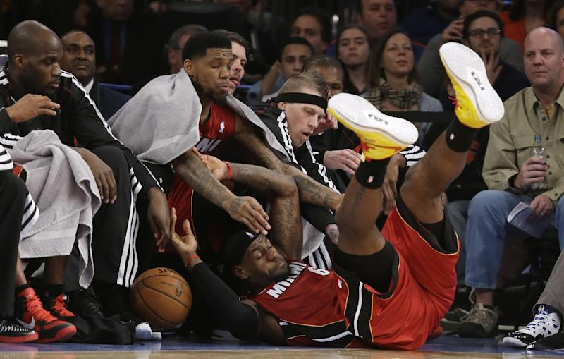 Miami Heat forward LeBron James (6) falls into the bench during the first half of an NBA basketball game against The New York Knicks at Madison Square Garden in New York, Sunday, March 3, 2013. (AP Photo/Kathy Willens)