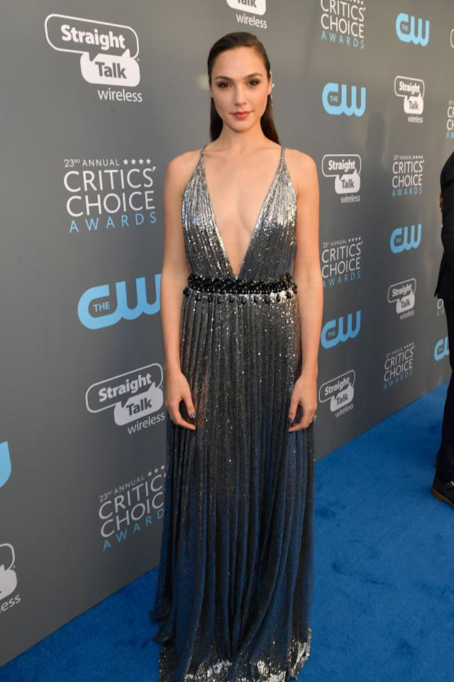 <p>The <em>Wonder Woman</em> star went with a metallic deep V-neck gown with a crisscross back and a black beaded waist. (Photo: Getty Images) </p>