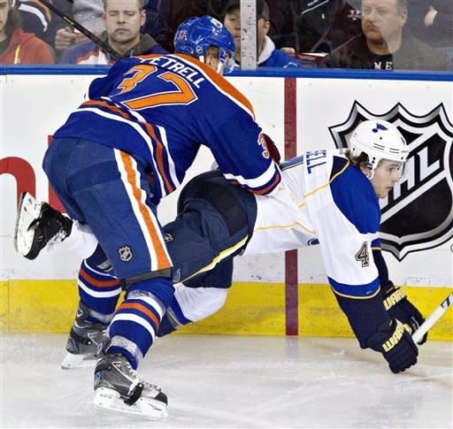 St. Louis Blues' Kris Russell, 4, is checked by Edmonton Oilers' Lennart Petrell during second period NHL hockey action in Edmonton, Alberta, on Saturday March 23, 2013. (AP Photo/The Canadian Press, Jason Franson)