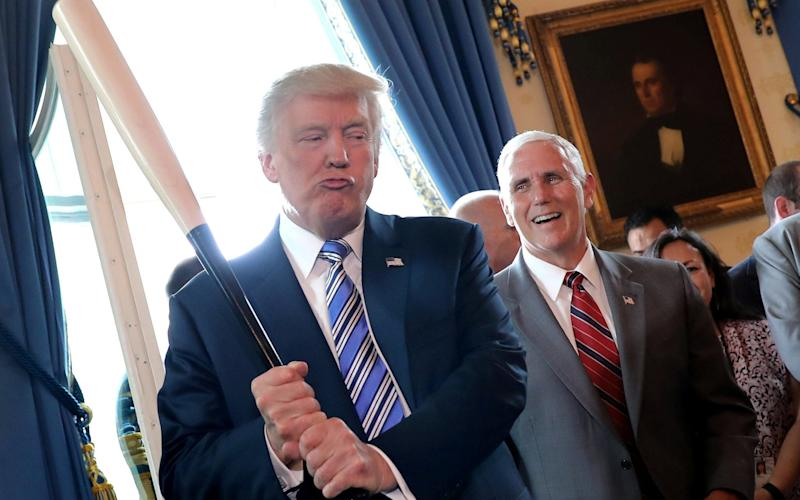 Vice President Mike Pence laughs as U.S. President Donald Trump holds a baseball bat as they attend a Made in America product showcase event - Credit: Reuters