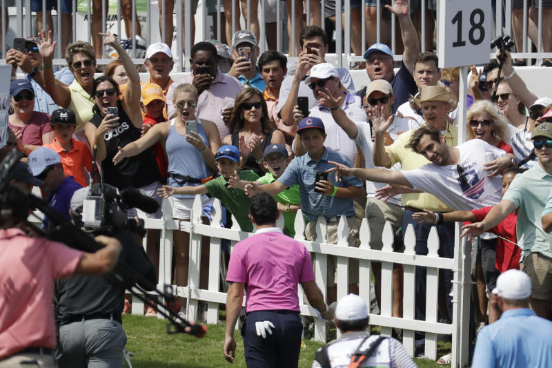 Fans cheer for Rory McIlroy, of Northern Ireland, as he leaves the 18th green during the third round of the World Golf Championships-FedEx St. Jude Invitational Saturday, July 27, 2019, in Memphis, Tenn. McIlroy birdied the 18th hole to finish the day at 12-under par, one stroke ahead of Brooks Kopeka. (AP Photo/Mark Humphrey)