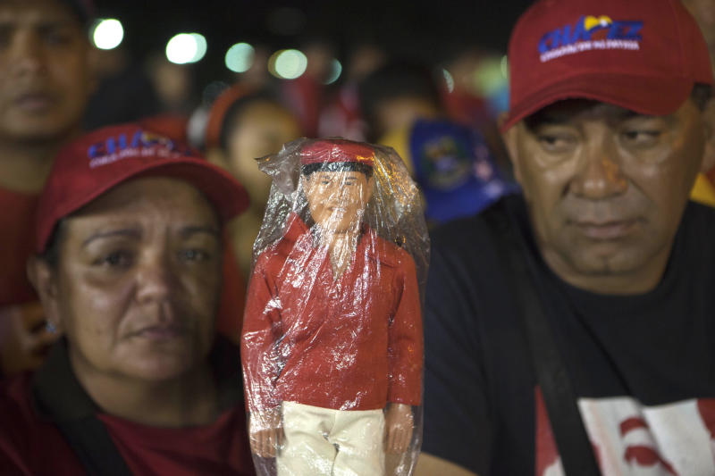 Supporters hold a doll depicting of the late President Hugo Chavez as they wait in line to see his body outside the Fort Tiuna military academy in Caracas, Venezuela, Wednesday, March 6, 2013. Chavez's body will lie in sate at the academy until his funeral, scheduled for Friday. (AP Photo/Esteban Felix)