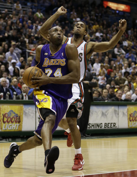 Los Angeles Lakers' Kobe Bryant (24) drives against Milwaukee Bucks' Ish Smith, rear, during the first half of an NBA basketball game, Thursday, March 28, 2013, in Milwaukee. (AP Photo/Jeffrey Phelps)