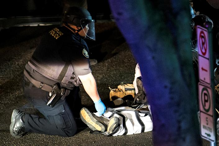 A police officer checks the body of a man who was shot dead at protests in Portland. (Mathieu Lewis-Rolland/Handout via Reuters)