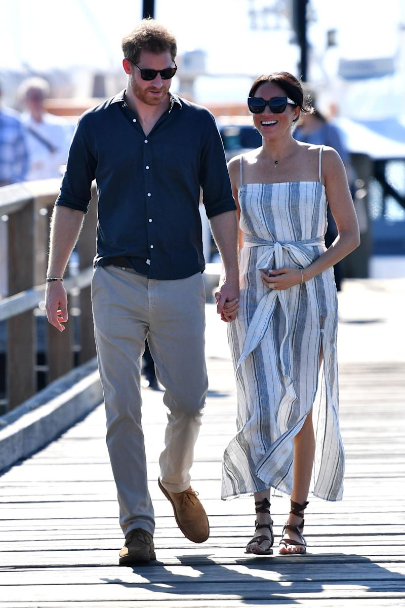 Britain's Prince Harry and his wife Meghan, the Duchess of Sussex walk to attend a meet-the-people session at Kingfisher Bay Resort on Fraser Island on October 22, 2018. - Prince Harry greeted an Aboriginal community on the stunning World Heritage-listed Fraser Island on October 22 as his pregnant wife Meghan took a break from official duties during the royal couple's Australian tour. (Photo by DARREN ENGLAND / POOL / AFP) (Photo credit should read DARREN ENGLAND/AFP via Getty Images)