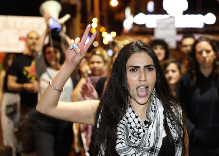 An Arab woman shouts slogans against Jewish nationalist religious groups that are buying up property in the Arab neighborhood of Jaffa, in Tel Aviv, Israel, Saturday, April 24, 2021. Historic Jaffa's rapid gentrification in recent years is coming at the expense of its mostly Arab lower class. With housing prices out of reach, discontent over the city's rapid transformation into a bastion for Israel's ultra-wealthy is reaching a boiling point. (AP Photo/Ariel Schalit)