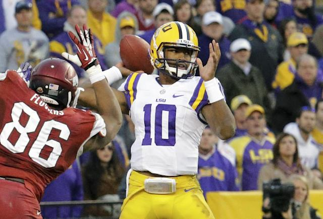 LSU quarterback Anthony Jennings (10) throws a pass as Arkansas defensive end Trey Flowers (86) rushes in during the second half of an NCAA college football game in Baton Rouge, La., Friday, Nov. 29, 2013. LSU defeated Arkansas 31-27. (AP Photo/Bill Haber)
