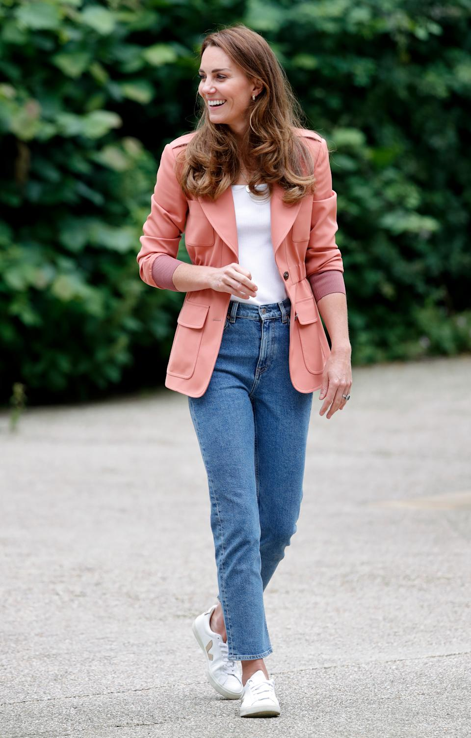 Kate Middleton wearing white Veja V-10 sneakers, blue jeans, a white shirt, and pink blazer during an engagement in London, England