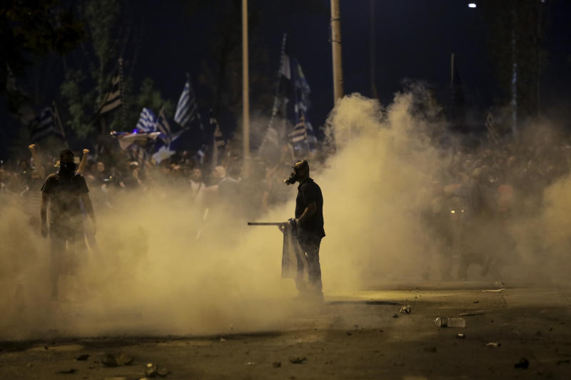 Protesters stand amid tear gas smoke during clashes with police at the northern Greek city of Thessaloniki, Saturday, Sept. 8, 2018. Greek police say about 6,000 protesters have tried to reach a venue where prime minister Alexis Tsipras is due to give a keynote address on the economy later Saturday and were pushed back with tear gas and stun grenades. (AP Photo/Dimitris Tosidis)
