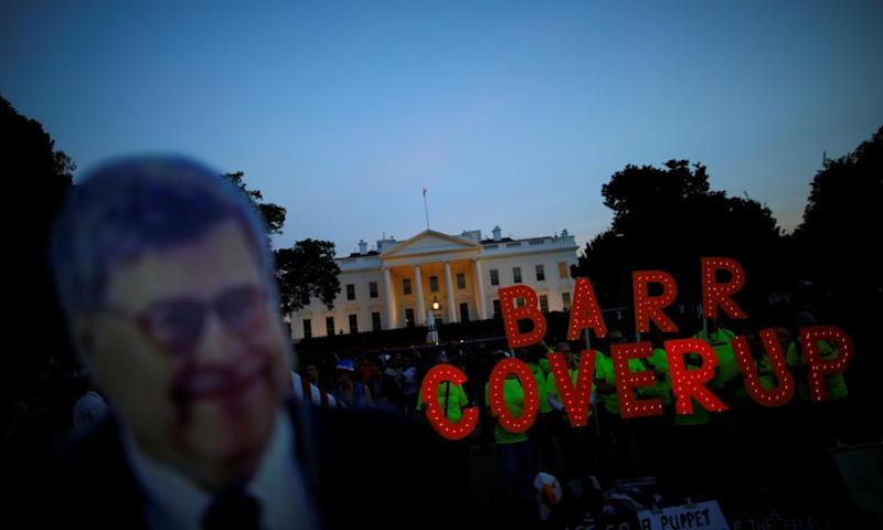 """A cardboard cutout of William Barr is seen as protesters hold signs which read """"Barr Coverup,"""" following the release of the Mueller report on 18 April 2019."""