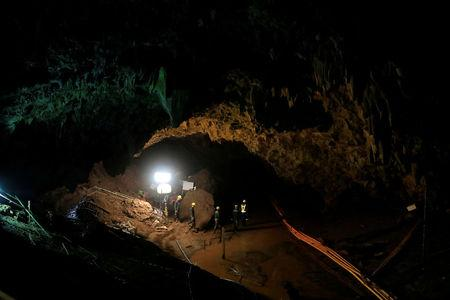 FILE PHOTO: Rescue workers follow 12 soccer players and their coach out of Tham Luang cave complex in the northern Thailand