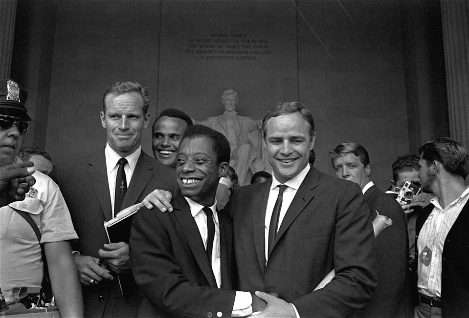 Actor Marlon Brando, right, poses with his arm around James Baldwin, author and civil rights leader, in front of the Lincoln statue at the Lincoln Memorial, August 28, 1963, during the March on Washington demonstration ceremonies which followed the mass parade.  Posing with them are actors Charlton Heston, left, and Harry Belafonte.  (AP Photo) ORG XMIT: APHS200 [Via MerlinFTP Drop]