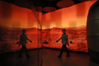 A woman walks past an exhibition depicting Mars landscape in Beijing on Friday, May 14, 2021. China says its Mars probe and accompanying rover are to land on the red planet sometime between early Saturday morning and Wednesday Beijing time. (AP Photo/Ng Han Guan)