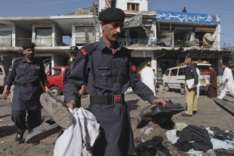 A soldier of Pakistani para military force collects the belongings of his colleagues after a bombing in Shabqadar near Peshawar, Pakistan on Friday, May 13, 2011. A police officer says the death toll in a pair of explosions outside a security force training center in northwest Pakistan has risen to 80. Liaqat Ali Khan says 66 victims in the attack Friday were recruits for the Frontier Corps. The attack is the bloodiest in Pakistan since the U.S. raid that killed the al-Qaida chief on May 2. Ahsanullah Ahsan, a spokesman for the Pakistani Taliban, has said the attack was in retaliation for bin Laden's death(AP Photo/Mohammad Sajjad)